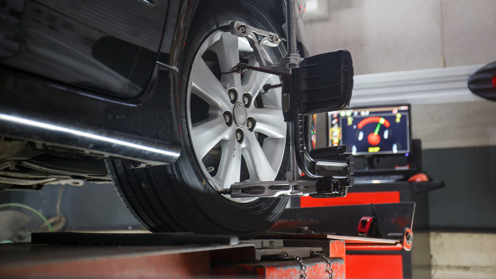 car-on-stand-in-garage-getting-wheel-alignment.jpg