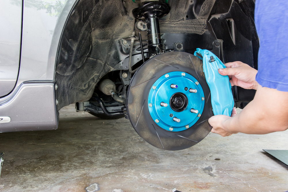 brake-caliper-being-adjusted-by-mechanic.jpg